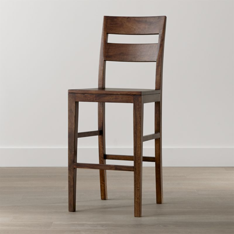 "Designed especially for bars, our taller 30"" Basque bar stool recalls the simple, rustic character of a European farmhouse antique. Generously proportioned bar stool with a strong yet comfortable presence is designed with a tall, modified double-slat back and deep seat. <NEWTAG/><ul><li>Sustainable solid mango wood</li><li>Rich honey stain with lacquer finish</li><li>Hand-planed wooden planks</li><li>Peg detailing</li><li>Naturally occurring grain and knots</li><li>Made in Indonesia</li></ul><br /><br />"