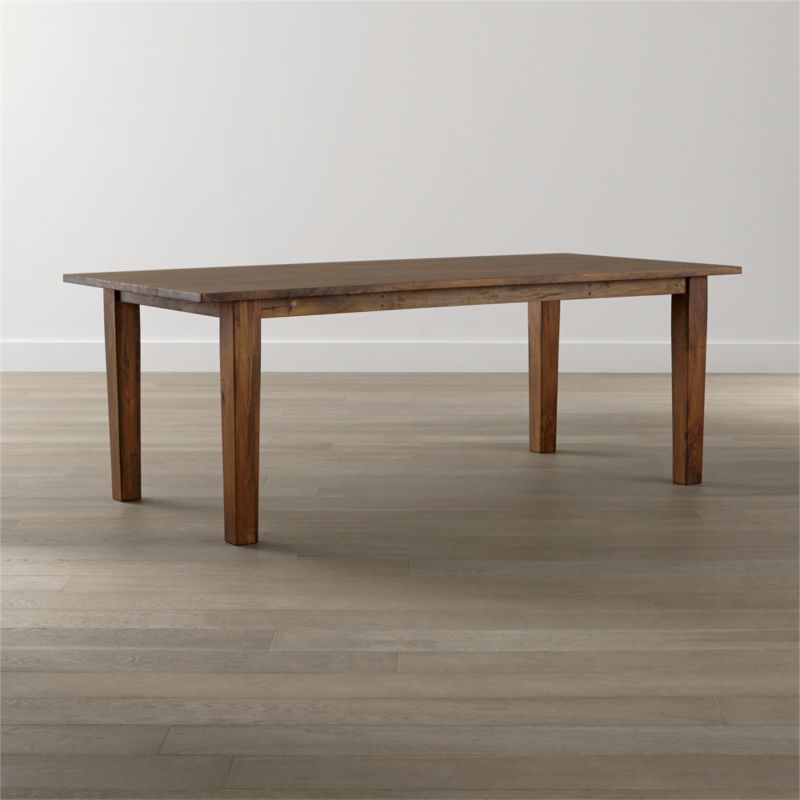 """Handcrafted of sustainable solid mango wood, the Basque 82"""" dining table recalls the heft and character of a European farmhouse antique. Simple and rustic, this dining table's bold proportions are enhanced with a rich waxed honey finish. <NEWTAG/><ul><li>Sustainable solid mango wood</li><li>Rich honey stain with lacquer and wax finish</li><li>Hand-planed wooden planks</li><li>Peg detailing</li><li>Naturally occurring grain and knots</li><li>Seats 8</li><li>Made in India</li></ul>"""