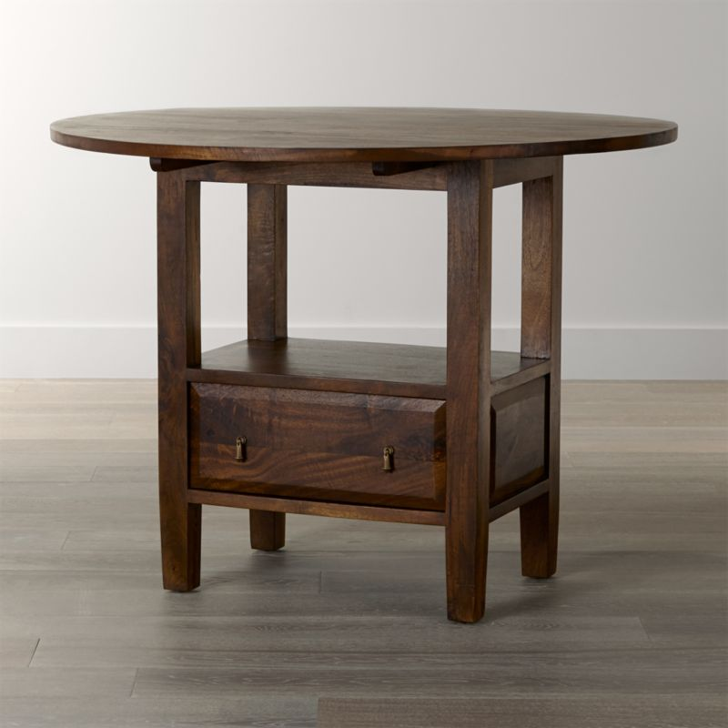 With the heft and character of a European farmhouse antique, the Basque high dining table is ideal for counter height dining in a kitchen, game room or bar. Simple and rustic, this table is handmade of sustainable solid mango wood, with substantial legs and hand-planed wooden planks finished with authentic peg detailing. A rich honey stain with lacquer finish is waxed to a soft sheen, enhancing the wood's natural open grain and beautifully unique knots. <NEWTAG/><ul><li>Sustainable solid mango wood</li><li>Rich honey stain with lacquer and wax finish</li><li>Hand-planed wooden planks</li><li>Peg detailing</li><li>Naturally occurring grain and knots</li><li>Drawer with cast brass drop knob pulls</li><li>Levelers</li><li>2 drop leaves</li><li>Seats 4</li><li>Made in India</li></ul>
