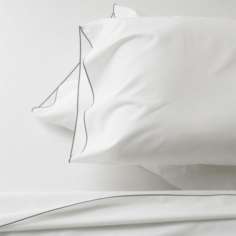 Clean, basic white bedding upgrades in soft, smooth cotton percale, beautifully contrasted with a graceful grey overlocking stitch on the flat sheet and pillow case. Generous fitted sheet pockets accommodate thicker mattresses. Sheet set includes one flat sheet, one fitted sheet and two standard pillow cases. Bed pillows also available.<br /><br /><NEWTAG/><ul><li>100% cotton percale</li><li>200-thread-count</li><li>Machine wash; tumble dry low</li><li>Made in Portugal</li></ul>