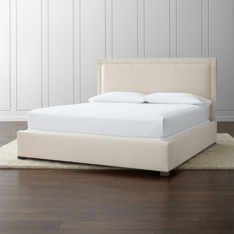The square sensibility and architectural polish of our Border bed take the edge off in a soft neutral cotton-poly blend over the linear frame. Self-welt detailing outlines the perimeter of the king bed, with horizontal and vertical lines that intersect at each corner. <NEWTAG/><ul><li>Frame is benchmade in the USA with certified sustainable hardwood that's kiln-dried to prevent warping</li><li>Soy-based polyfoam cushioning</li><li>Solid maple legs with brown finish</li><li>3 metal slats with 3 center support legs</li><li>Accommodates mattress and box spring (sold separately)</li><li>Maximum weight capacity: 800 lbs. (includes weight of mattress, box spring and occupants)</li><li>Material origin: see swatch</li><li>Made in North Carolina, USA</li></ul><br />