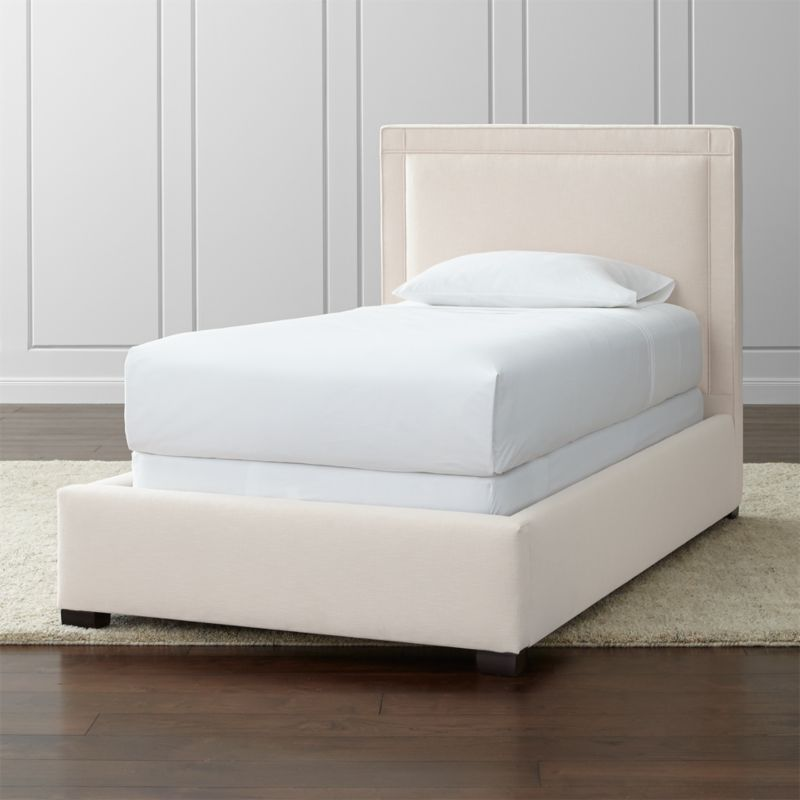 The Border twin bed's square sensibility takes the edge off in a soft neutral cotton-poly blend over a linear frame. Self-welt detail adds architectural polish, outlining the perimeter of the twin bed with horizontal and vertical lines intersecting at each corner. <NEWTAG/><ul><li>Frame is benchmade in the USA with certified sustainable hardwood that's kiln-dried to prevent warping</li><li>Soy-based polyfoam cushioning</li><li>Solid maple legs with brown finish</li><li>3 metal slats with 3 center support legs</li><li>Accommodates mattress and box spring (sold separately)</li><li>Maximum weight capacity: 500 lbs. (includes weight of mattress, box spring and occupants)</li><li>Material origin: see swatch</li><li>Made in North Carolina, USA</li></ul>