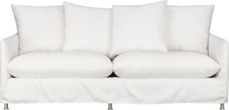 "This sleek white slipcovered sofa looks like it could be right at home in a modern urban loft. But don't bother to come inside—our eco-friendly Catalina collection is designed to live carefree outdoors under blue skies. Under that UV-, fade- and moisture-resistant Sunbrella® sailcloth slipcover (yes, it's even machine-washable), you'll find a thoughtfully crafted sofa made in the USA at the same furniture workshop as many of our living room upholstered collections. A 15-ply outdoor-grade sustainable birch plywood frame subtly slopes the seat deck front to back to drain water properly from an open bottom slot. Plush cushions are a reticulated open-cell foam that allows water to drain. Comfortable back cushions and pillows are protected by waterproof ticking. Upholstered in Sunbrella base cloth sand, an open-weave fabric that accelerates drainage and allows cushions and pillows to breathe, with a bottom zipper to drain water and release moisture.<br /><br />After you place your order, we will send a fabric swatch via next day air for your final approval. We will contact you to verify both your receipt and approval of the fabric swatch before finalizing your order.<br /><br /><NEWTAG/><ul><li>Eco-friendly construction</li><li>Outdoor-grade sustainable birch plywood frame</li><li>Seat cushions are mildew-resistant, reticulated open-cell foam</li><li>Back cushions and pillows are filled with outdoor recycled fiber in a waterproof ticking</li><li>Slipcovered in 100% Sunbrella solution-dyed acrylic</li><li>Machine wash the removable slipcovers; line dry</li><li>Includes four 23"" throw pillows</li><li>Rustproof brushed aluminum legs</li><li>See additional frame options below</li></ul>"