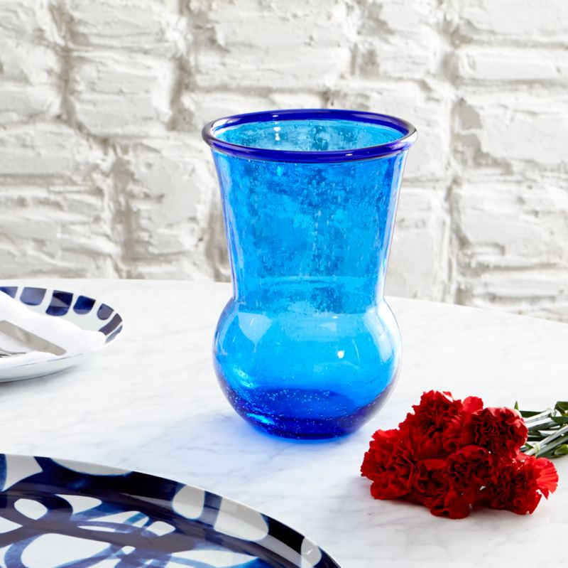 Paolo Navone's palette of blues is inspired by her world experiences and life by the sea. From the deep blues found in Moroccan tiles and the Turkish eye to the aquamarine seas of the Greek Isles, a range of blues infuses the Como collection with coastal color and flair. Tulip-shaped vase bubbles like the tide, handcrafted of thick blue glass and rimmed with a ring of cobalt.<br /><br /><NEWTAG/><ul><li>Designed by Paola Navone exclusively for Crate and Barrel</li><li>Handcrafted</li><li>Glass</li><li>Hand wash</li><li>Made in Thailand</li></ul>