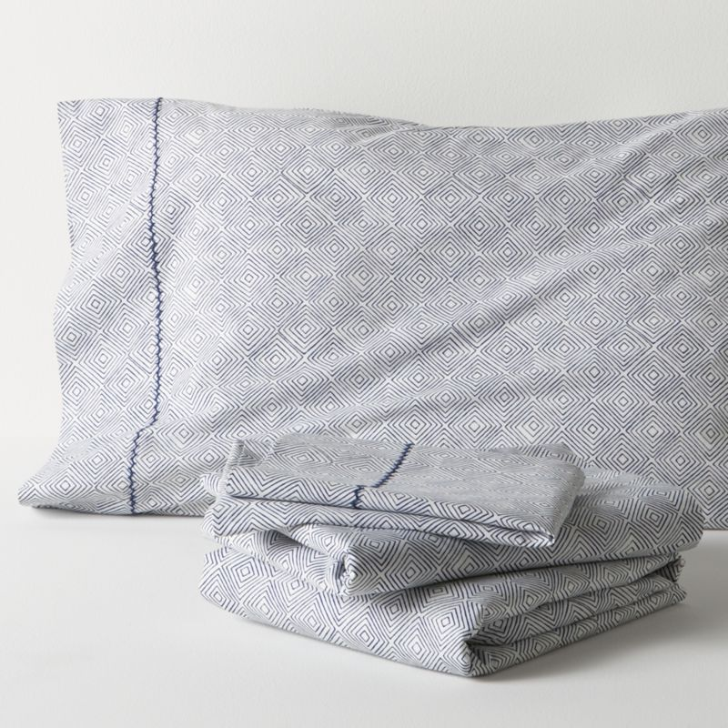 A subtle optic of concentric diamonds is screen-printed navy on neutral to layer with patterned or solid bedding. Soft cotton percale sheets are joined by matching cases, embellished with a single row of hand-embroidered chain stitching. Sheet set includes one flat sheet, one fitted sheet and two standard pillowcases. Bed pillows also available.<br /><br /><NEWTAG/><ul><li>100% cotton percale</li><li>200-thread-count</li><li>Machine wash, tumble dry low, warm iron as needed</li><li>Made in India</li></ul>