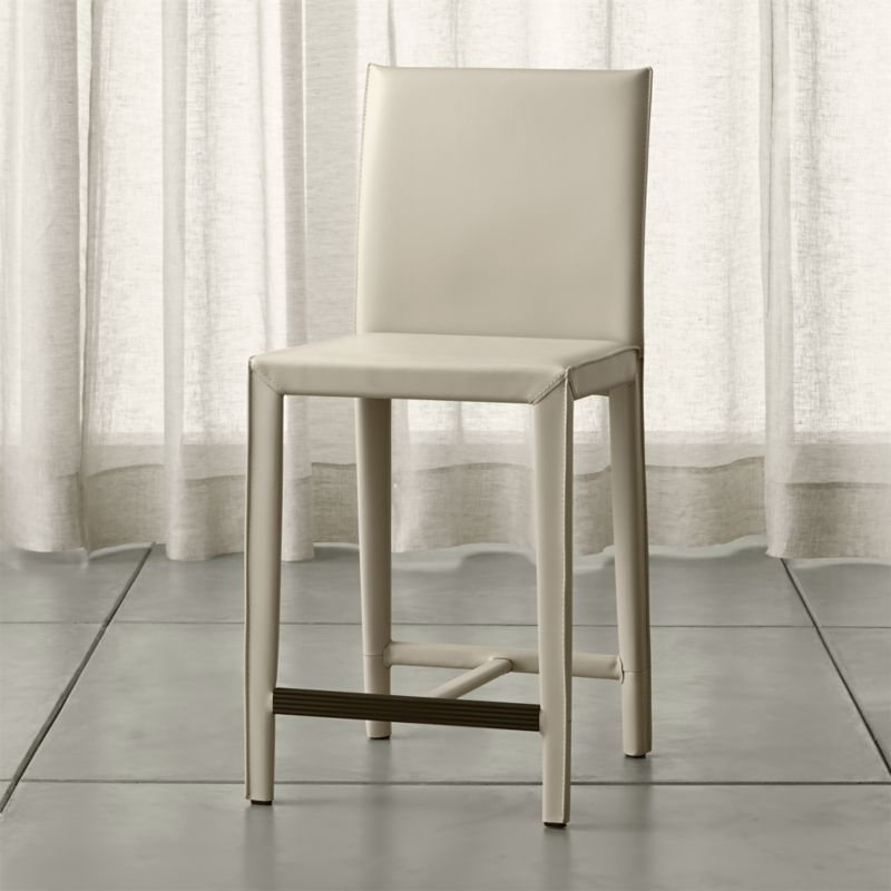 In a reinvention of classic Italian design with a focus on comfort and value, our Folio counter stool gets wrapped in warm, oyster white, bonded leather. Attention-getting details make the Folio seating collection a customer favorite, including trim mitered corners, flange seaming and stitching accentuating each piece's good looks. <NEWTAG/><ul><li>Welded steel frame</li><li>Polyfoam seat cushion with fiber wrap</li><li>Mitered cut and stitched leather</li><li>Flange seaming</li><li>Grooved footrest</li><li>Material origin: see swatch</li><li>Made in China</li></ul>