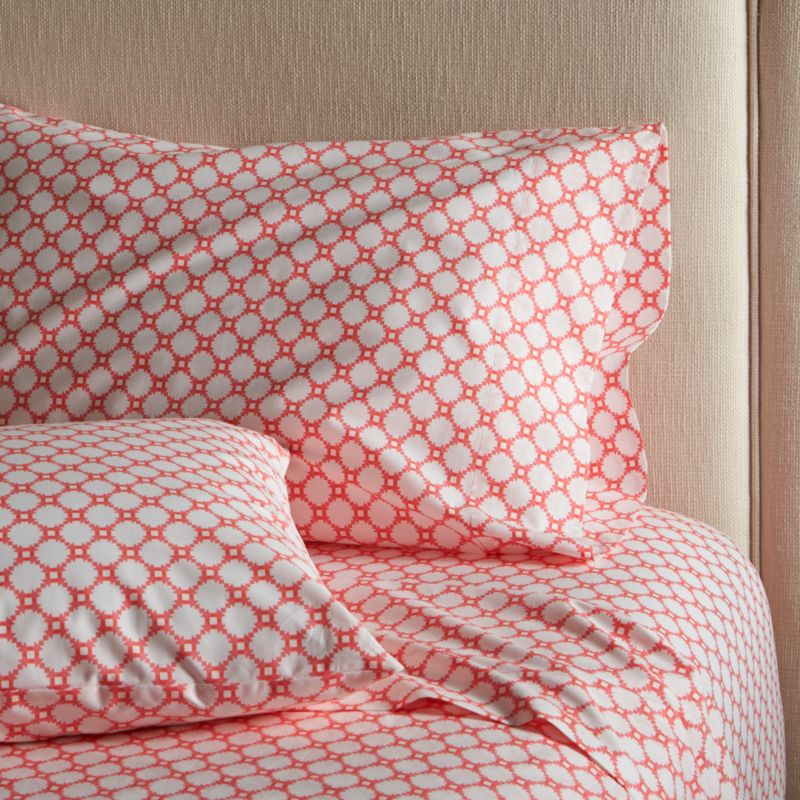 "Classic geometric quilting pattern updates in sunny coral and white as a sunny, streamlined graphic by London designer Genevieve Bennett, printed on soft cotton percale. Scaled-down motif coordinates beautifully with boldly patterned Genevieve bed linens. Sheet set includes one flat sheet, one fitted sheet and king pillowcases. Bed pillows also available.<br /><br /><NEWTAG/><ul><li>Designed by Genevieve Bennett</li><li>100% cotton percale</li><li>200-thread-count</li><li>Fitted sheet has 16"" pocket</li><li>Machine wash cold, tumble dry low; warm iron as needed</li><li>Made in Portugal</li></ul>"