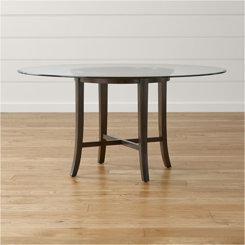 """With its distinctive """"halo"""" effect, this striking dining table features a flat glass top with a deep light-refracting reverse bevel supported by a solid chestnut wood base with cross brace and slightly flared legs that extend from the apron. The halo is echoed in the open ring top of the frame, finished with a rich, deep ebony stain. <NEWTAG/><ul><li>Solid chestnut base with deep ebony finish</li><li>Clear ½""""-thick glass top with reverse bevel and polished edge</li><li>BreathingJoinery ™</li><li>Plastic glides</li><li>Seats 6</li><li>Made in China</li></ul>"""