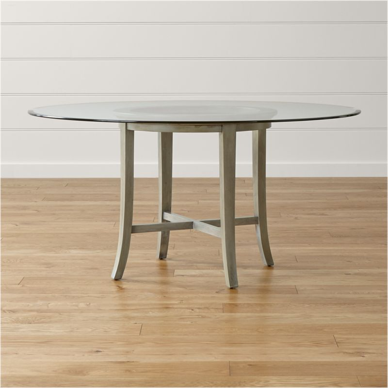 "With its distinctive ""halo"" effect, this striking dining table features a flat glass top with a deep light-refracting reverse bevel in a halo effect that's echoed in the open ring top of the frame. Supported by a solid chestnut wood base with cross brace and slightly flared legs that extend from the apron, the Halo 60"" dining table is finished with a soft grey stain that's sheer enough to showcase the wood's natural grain. <NEWTAG/><ul><li>Solid chestnut base with grey-washed lacquer finish</li><li>Clear ½""-thick glass top with reverse bevel and polished edge</li><li>BreathingJoinery ™</li><li>Plastic glides</li><li>Seats 6</li><li>Made in China</li></ul>"