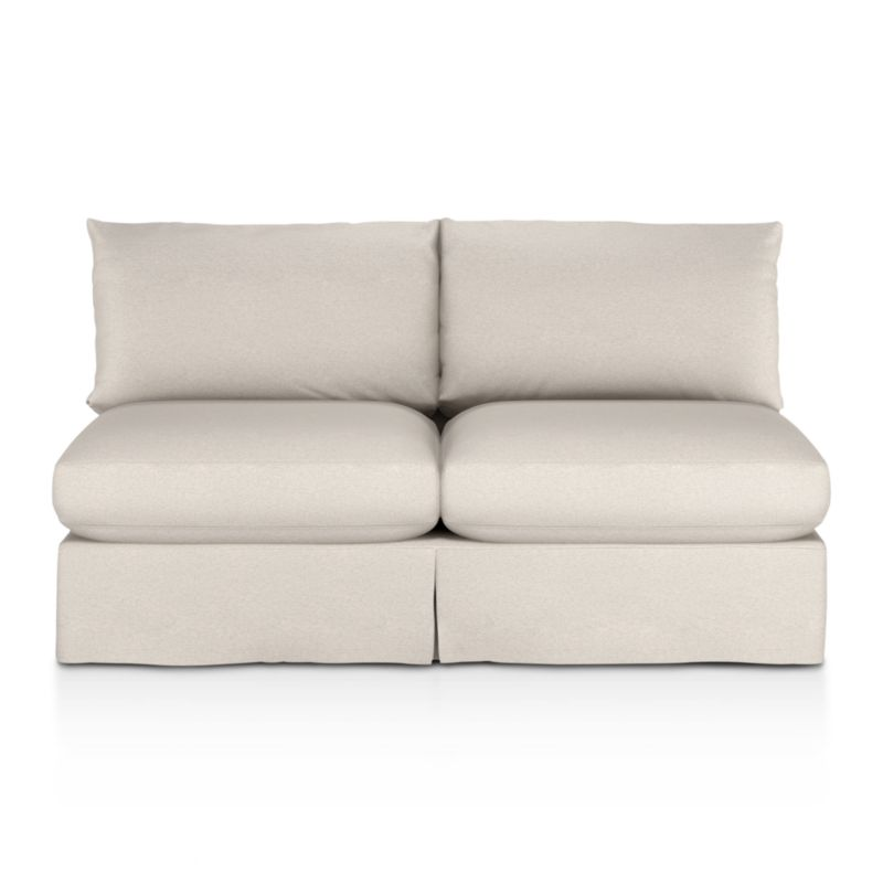 """Tailored to fit our Lounge Slipcovered Armless Loveseat, smart denim slipcover is tailored with a kickpleat skirt and jumbo double topstitch outlining its plump, deep cushions.<br /><br />Additional <a href=""""http://crateandbarrel.custhelp.com/cgi-bin/crateandbarrel.cfg/php/enduser/crate_answer.php?popup=-1&p_faqid=125&p_sid=DMUxFvPi"""">slipcovers</a> available below and through stores featuring our Furniture Collection.<br /><br />After you place your order, we will send a fabric swatch via next day air for your final approval. We will contact you to verify both your receipt and approval of the fabric swatch before finalizing your order.<br /><br /><NEWTAG/><ul><li>100% cotton</li><li>Machine washable</li><li>Jumbo contrast topstitching detail</li><li>Made in North Carolina, USA</li></ul><br />"""