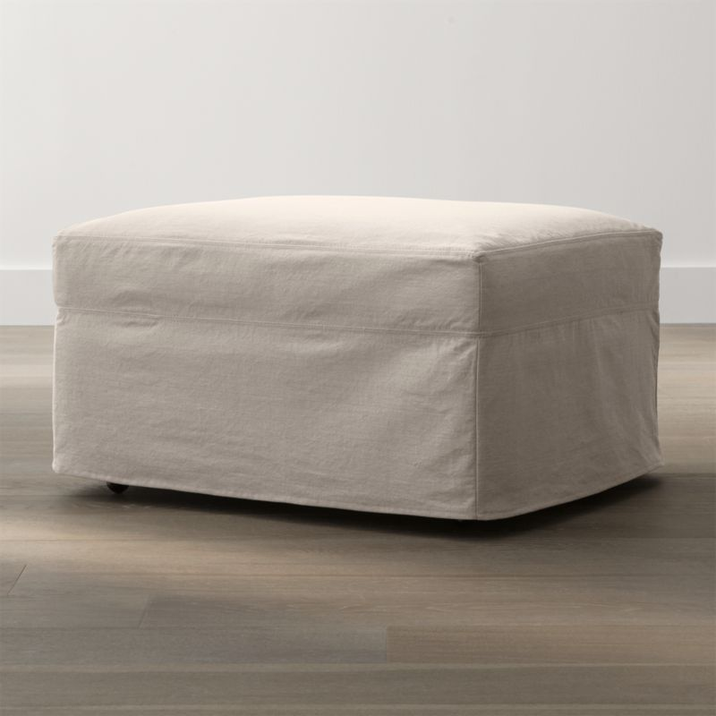"""Tailored to fit our Lounge Slipcovered Ottoman, smart denim slipcover is tailored with a kickpleat skirt and jumbo double topstitch outlining.<br /><br />Additional <a href=""""http://crateandbarrel.custhelp.com/cgi-bin/crateandbarrel.cfg/php/enduser/crate_answer.php?popup=-1&p_faqid=125&p_sid=DMUxFvPi"""">slipcovers</a> available below and through stores featuring our Furniture Collection.<br /><br />After you place your order, we will send a fabric swatch via next day air for your final approval. We will contact you to verify both your receipt and approval of the fabric swatch before finalizing your order.<br /><br /><NEWTAG/><ul><li>100% cotton</li><li>Machine washable</li><li>Jumbo contrast topstitching detail</li><li>Made in North Carolina, USA</li></ul><br /><br />"""