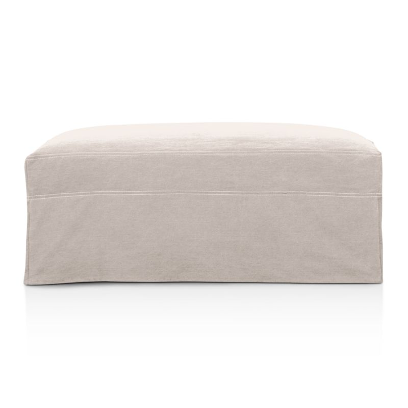 """Tailored to fit our Lounge Slipcovered Storage Ottoman, smart denim slipcover is tailored with a kickpleat skirt and jumbo double topstitch outlining.<br /><br />Additional <a href=""""http://crateandbarrel.custhelp.com/cgi-bin/crateandbarrel.cfg/php/enduser/crate_answer.php?popup=-1&p_faqid=125&p_sid=DMUxFvPi"""">slipcovers</a> available below and through stores featuring our Furniture Collection.<br /><br />After you place your order, we will send a fabric swatch via next day air for your final approval. We will contact you to verify both your receipt and approval of the fabric swatch before finalizing your order.<br /><br /><NEWTAG/><ul><li>100% cotton</li><li>Machine washable</li><li>Jumbo contrast topstitching detail</li><li>Made in North Carolina, USA</li></ul><br />"""