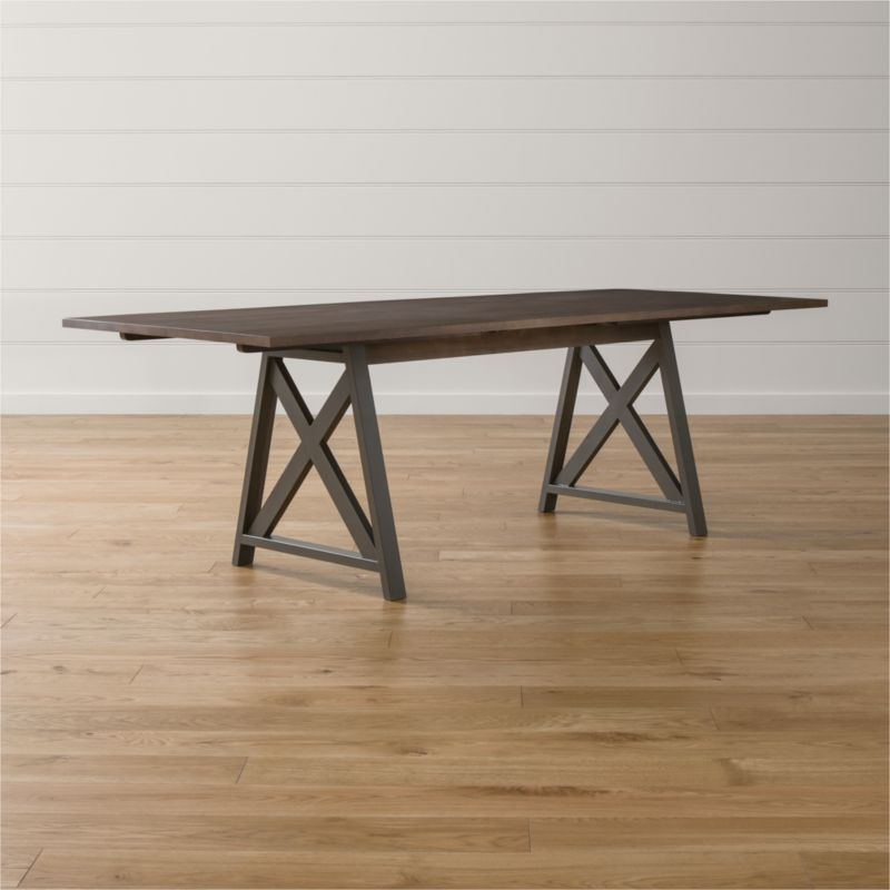"Casual, urban table glides on a hidden mechanical pulley system to transport gatherings from small to grand. Trestle-styled steel legs finished dark grey structure the table with a warm ash veneer top that easily expands to seat 10. <NEWTAG/><ul><li>Designed by Mark Daniel of Slate</li><li>Ash veneer over engineered wood</li><li>Solid poplar apron with grey wash finish</li><li>Steel legs with dark matte grey finish</li><li>Hidden pull-glide system</li><li>Seats six; 10 with one 20"" leaf</li><li>Made in Vietnam</li></ul><br />"