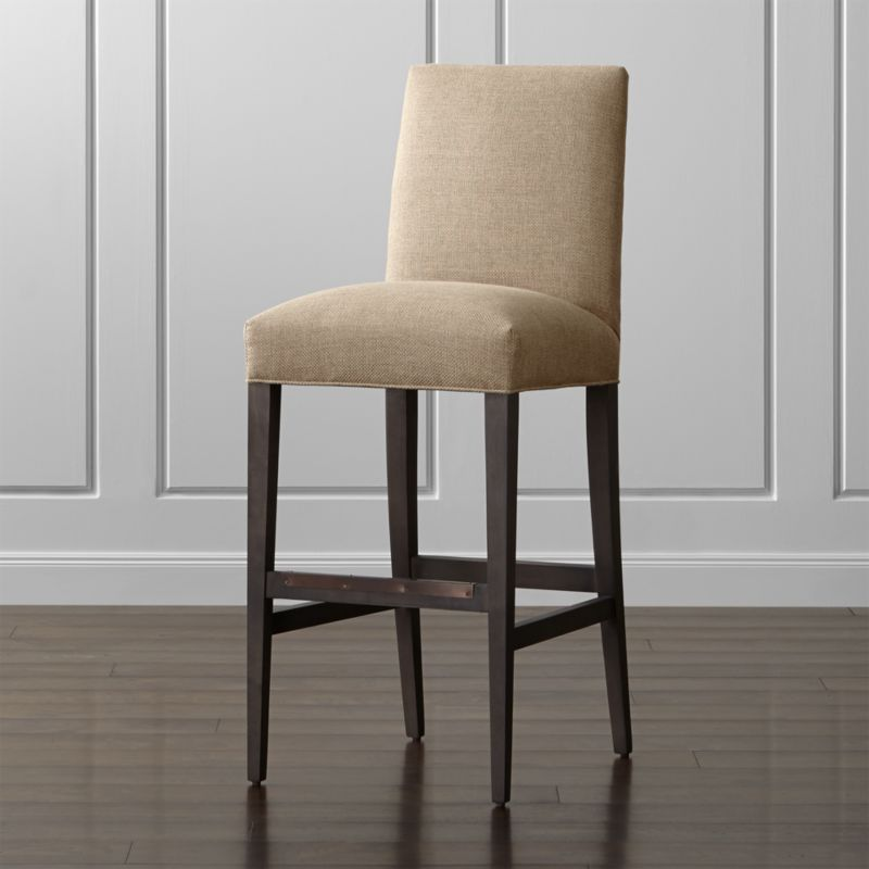 Sit tall with the classic, polished proportions and casual formality of our scaled-up Miles bar stool. Sized especially for the bar, this taller stool features a comfortably padded tight seat and back upholstered in a durable synthetic fabric. The hardwood legs with a warm grey finish taper gracefully to the floor, with the added benefit of a convenient footrest. The Miles Bar Stool is a Crate and Barrel exclusive.<br /><br /><NEWTAG/><ul><li>Certified-sustainable solid hardwood frame</li><li>Soy-based polyfiber tight seat and tight back</li><li>Solid hardwood legs with a warm grey finish</li><li>Plastic glides</li><li>Material origin: see swatch</li><li>Made in North Carolina, USA</li></ul>