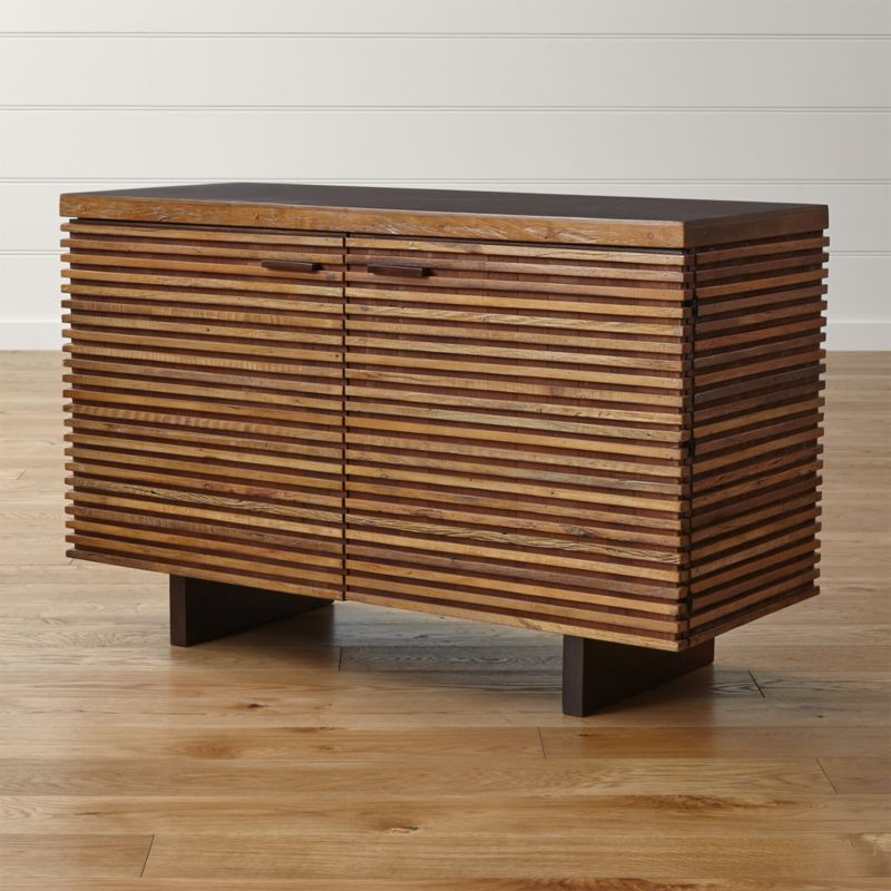 Zen-meets-Prairie-Style dining storage, crafted of artfully repurposed, naturally aged peroba wood. Reclaimed from the siding and floors of old buildings in Brazil, this exotic wood is restored and handcrafted to create the dynamic presence of the Paloma I small sideboard. Crafted of hand-laid strips of peroba wood, the Paloma I small sideboard's frame supports a top of mahogany veneer over engineered wood. Solid mahogany pulls are finished in a warm java brown stain, and cord management cutouts allow for use as a media console. <NEWTAG/><ul><li>Reclaimed peroba wood, engineered wood and mahogany veneer</li><li>Java brown finish with water-based clear lacquer topcoat on top, pulls and shelves</li><li>Each piece is unique due to the natural aging process of peroba wood</li><li>2 drawers and 2 doors with solid mahogany pulls</li><li>1 adjustable shelf</li><li>Metal glides</li><li>Leg levelers</li><li>Cord management cutouts</li><li>Made in Indonesia</li></ul><br />