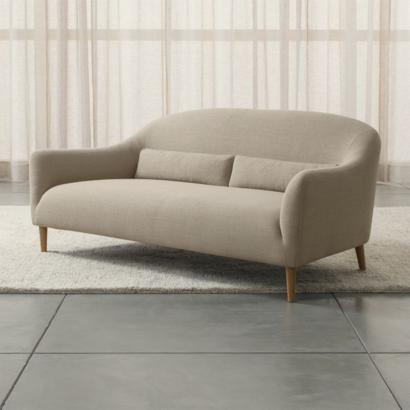 Sleek curves flare out to invite you in to this affordable furniture collection for small rooms and apartments by London-based designer Bethan Gray. Every turn of the sofa's graceful tight back and plush seat is hugged by a textured, linen-blend weave. Two coordinating kidney pillows support your lower back; tapered legs are made of solid white oak. <NEWTAG/><ul><li>Designed by Bethan Gray</li><li>Frame is made with a certified sustainable solid wood and engineered hardwood</li><li>Sinuous wire spring and synthetic web suspension systems</li><li>High-resiliency, high-density foam and polyfiber back and seat cushions</li><li>Fiber-down blend kidney pillows encased in downproof ticking</li><li>Solid white oak legs with clear lacquer finish</li><li>Material origin: see swatch</li><li>Made in China</li></ul>