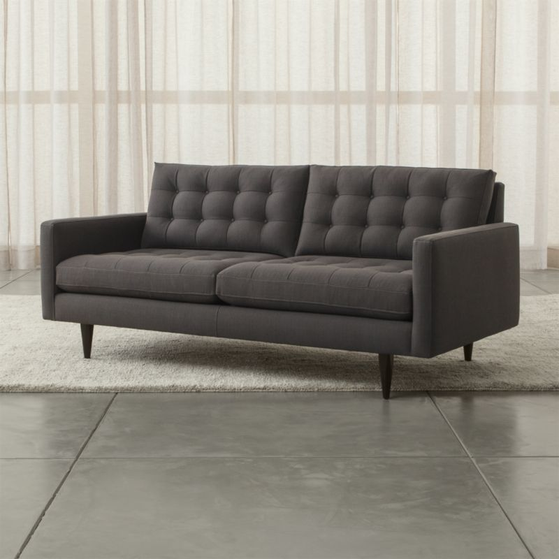 Petrie is a distinct living room sofa that sits at the intersection of mid-century and today, with clean lines and tailored cushions expertly button-tufted by hand. <NEWTAG/><ul><li>Frame is benchmade in the USA with certified sustainable hardwood that's kiln-dried to prevent warping</li><li>Sinuous wire spring suspension</li><li>Soy-based polyfoam seat and back cushions wrapped in fiber-down blend and encased in downproof ticking</li><li>Hardwood legs finished with a dark ebony stain</li><li>Topstitched and button-tufted detail</li><li>Material origin: see swatch</li><li>Made in Virginia, USA</li></ul>