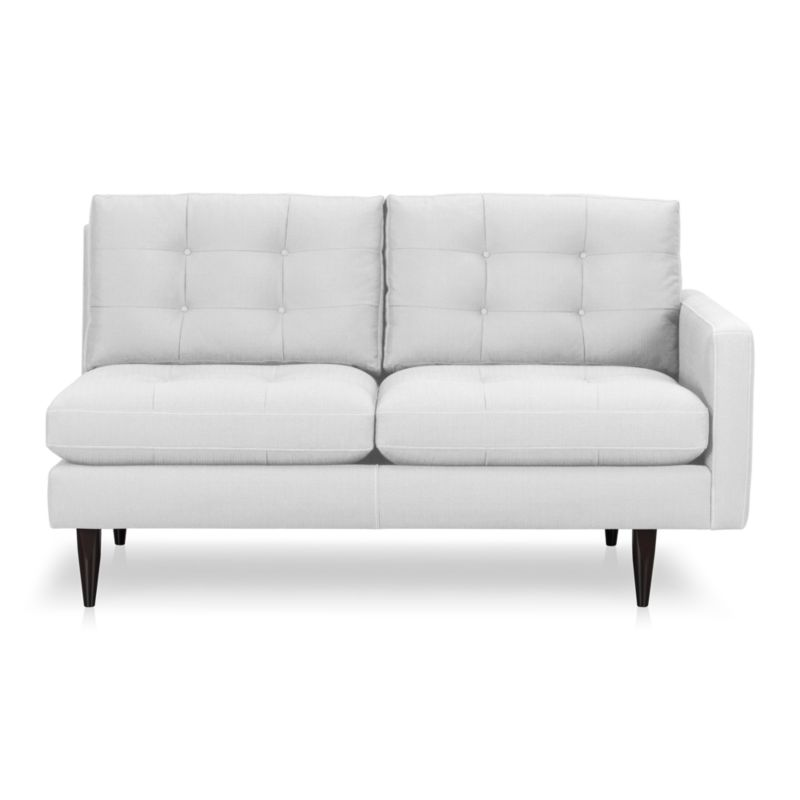 It was the most familiar furniture shape of the 1960s. And now it's coming back to a living room near you. This time around, it has tufted and buttoned cushions for a more classic, tailored look that sits deep and firm, but lets you slouch in comfort. Clean white cotton-poly blend fabric is treated with a new stain-repellant system that's actually in each fiber. Petrie is authentically styled light and lean with slim topstitched track arms and trim hardwood legs stained a dark ebony finish called deco.<br /><br />After you place your order, we will send a fabric swatch via next day air for your final approval. We will contact you to verify both your receipt and approval of the fabric swatch before finalizing your order.<br /><br /><NEWTAG/><ul><li>Eco-friendly construction</li><li>Certified sustainable, kiln-dried hardwood frame</li><li>Seat cushions are soy-based polyfoam with fiber wrapped in downproof ticking</li><li>Back cushions are a blend of virgin and recycled fibers</li><li>Sinuous wire spring suspension</li><li>Stain-resistant finish for maximum cleanability</li><li>Cotton-polyester blend fabric</li><li>Topstitched and button-tufted detail</li><li>Benchmade</li><li>See additional frame options below</li><li>Made in Virginia, USA</li></ul>