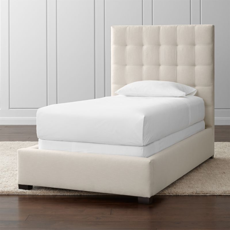Float off to sleep on our tailored Quadrant twin bed, lining up on the grid as a tall presence for the contemporary bedroom. The twin bed with plush headboard is wrapped in a soft, cotton-poly blend fabric with buttonless tufting adding casual definition and visual interest. The Quadrant Full Bed is a Crate and Barrel exclusive.<br /><br /><NEWTAG/><ul><li>Certified sustainable kiln-dried hardwood frame</li><li>Soy-based polyfoam cushioning</li><li>Solid maple legs with brown finish</li><li>3 metal slats with 3 center support legs</li><li>Accommodates mattress and box spring (sold separately)</li><li>Maximum weight capacity: 500 lbs. (includes weight of mattress, box spring and occupants)</li><li>M