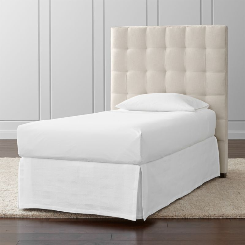 The twin size of our Quadrant headboard lines up on the grid as a tall presence for the contemporary bedroom. Each twin headboard is wrapped in a soft, cotton-poly blend fabric, with buttonless tufting adding casual definition and visual interest. The Quadrant Twin Headboard is a Crate and Barrel exclusive.<br /><br /><NEWTAG/><ul><li>Frame is benchmade in the USA with certified sustainable hardwood that's kiln-dried to prevent warping</li><li>Soy-based polyfoam cushioning</li><li>Solid maple legs with brown finish</li><li>Headboard requires a bed frame (sold separately)</li><li>When attached to Crate and Barrel bed frame no additional hardware required; accommodates mattress and box spring (sold separately)</li><li>Non-Crate and Barrel bed frame may require a Modi-Plate Kit (sold separately)</li><li>Material origin: see swatch</li><li>Made in North Carolina, USA</li></ul>