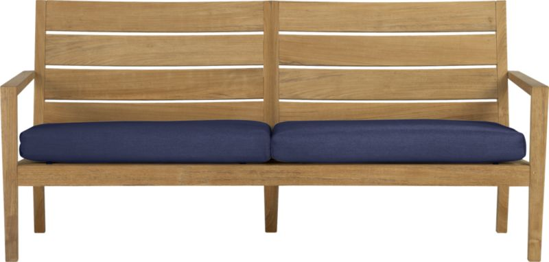 Our eco-friendly Regatta teak lounge collection cuts a clean, classic profile in a bold wide-slat design. Relax on a full-size sofa with sleek arms and comfortable angled backs. All pieces are handcrafted of plantation-grown teak supported by the TFT, a nonprofit organization that promotes responsible forest conservation. We recommend allowing the unfinished teak to weather to a silvery grey. To maintain the natural color, use our Golden Care® Teak Protector. Cushions are fade- and mildew-resistant Sunbrella acrylic in deep indigo blue. Regatta dining collection also available.<br />After you place your order, we will send a fabric swatch via next day air for your final approval. We will contact you to verify both your receipt and approval of the fabric swatch before finalizing your order.<br /><br /><NEWTAG/><ul><li>Solid teak harvested from plantations working with TFT</li><li>Unfinished</li><li>Mortise-and-tenon joinery</li><li>Stainless steel hardware</li><li>Cushion is fade- and mildew-resistant Sunbrella acrylic</li><li>Polyester batting and foam cushion fill</li><li>Cushion is secured with fabric tab fasteners</li><li>Spot clean the cushion cover</li><li>Made in Indonesia and Mexico </li></ul>