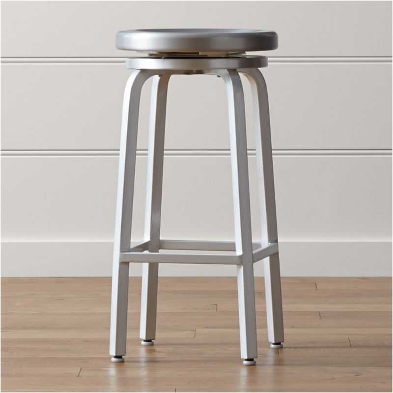 This industrial, contemporary brushed aluminum bar stool has a bar-appropriate height and offers the classic 360-degree spin, with ball bearing action for a smooth ride. <NEWTAG/><ul><li>Traditional base design with foot rungs</li><li>Foot caps to protect floor surfaces</li><li>Clear lacquer finish</li><li>Made in China</li></ul><br /><br />