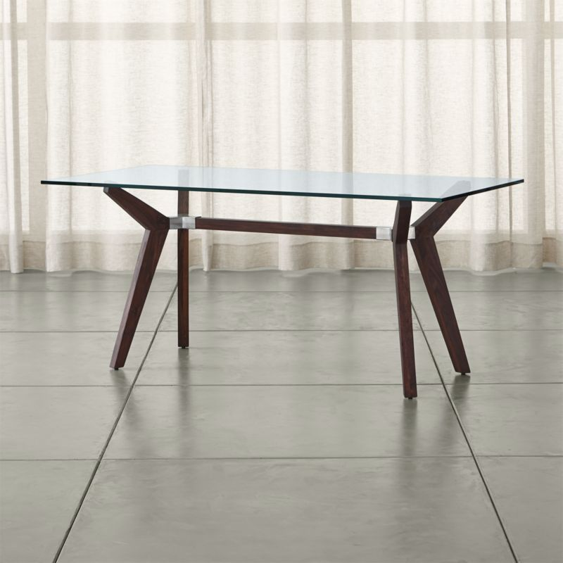 "The statement-making Strut work table offers clean, modern lines elegant enough for the dining room. A substantial glass top floats on dramatically-angled shesham wood legs with a matte walnut stain. <NEWTAG/><ul><li>Shesham with walnut stain, water based lacquer and wax topcoat</li><li>As with all solid woods, expansion and contraction may occur with seasonal changes in humidity</li><li>5/8"" glass top</li><li>Steel joints</li><li>Seats six</li><li>Made in India and China </li></ul><br />"