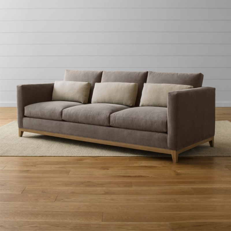 Relaxing all conventions about what a living room sofa can be, our Taraval 3-seat sofa is a casually elegant seating option upholstered in all-natural cotton with an exposed solid oak base in a grey, weathered finish. Stonewashed kidney cushions in 100 percent linen are lofted with down to hug your lower back in comfort. <NEWTAG/><ul><li>Frame is benchmade in the USA with eco-friendly, certified sustainable hardwood that's kiln-dried to prevent warping</li><li>Solid oak legs and base in a weathered grey finish</li><li>Eight-way, hand-tied spring suspension system</li><li>Soy-based polyfoam seat cushions with innerspring coil system, wrapped in polyfiber and feather-down blend and encased in downproof ticking</li><li>Polyfiber and feather-down blend back cushions and kidney pillows encased in downproof ticking</li><li>Includes 3 kidney pillows</li><li>Material origin: see swatch</li><li>Made in North Carolina, USA</li></ul>